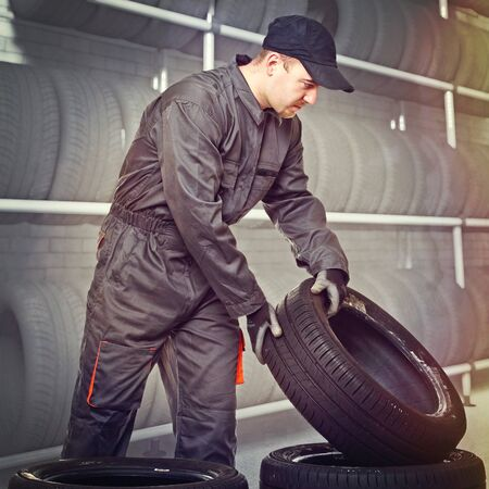 garage worker move some tires Stock Photo - 16380492
