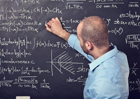 matematica: retrato del profesor de sexo masculino en el trabajo