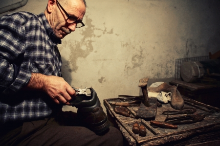 old leather: cobbler at work with old tools
