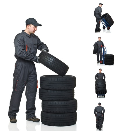 young mechanic move tires isolated on white background photo