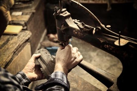 riparatore: calzolaio al lavoro con macchina da cucire Archivio Fotografico