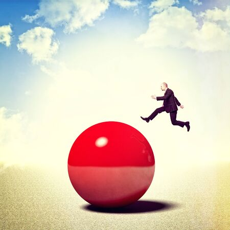 try: businessman try to jump over red ball