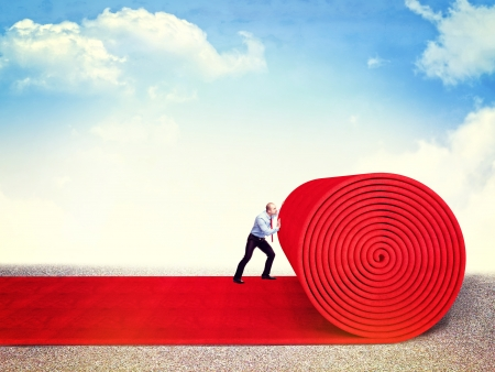 fabric roll: man roll huge red carpet Stock Photo