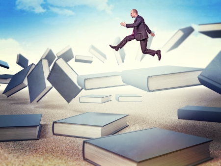 adult education: businessman jump from flying books Stock Photo