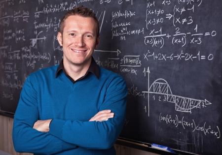 young caucasian teacher portrait with blackboard background
