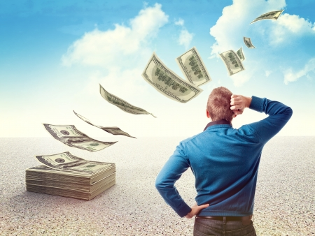 dinero volando: hombre mira su dinero volando Foto de archivo