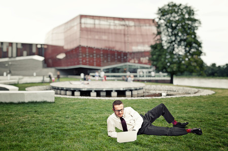 netbook: businessman rest on grass and use netbook