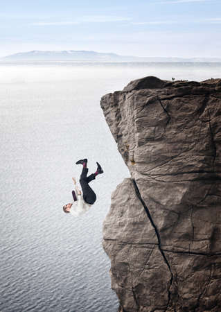 proble: businessman fall from cliff sea background Stock Photo