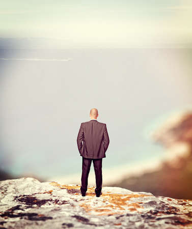 standing businessman on cliff looking the sea Stock Photo - 29855124