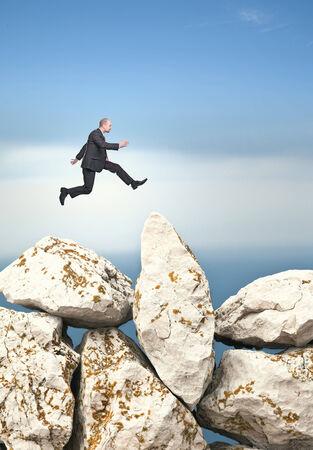 businessman jump over huge rock Stock Photo - 30026535