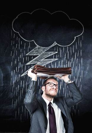 businessman and bad weather cloud on blackboard photo