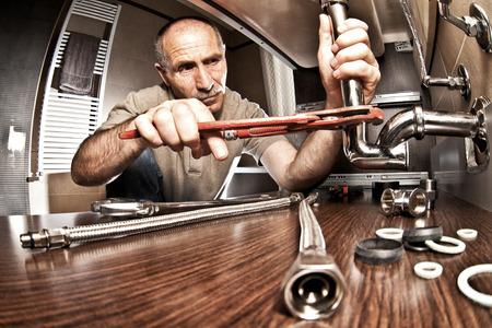 fontaneria: retrato de fontanero mayor en el trabajo
