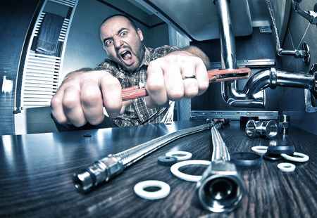 plumbing tools: portrait of angry plumber at work