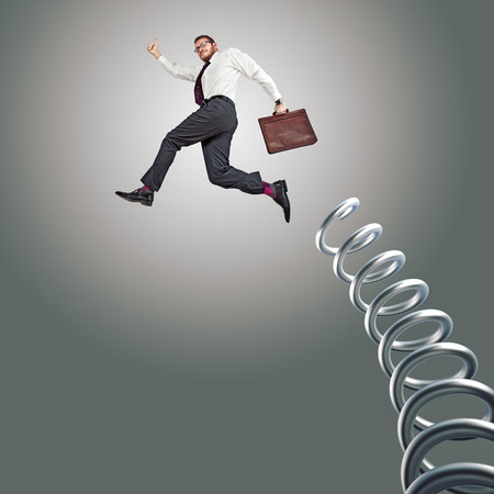 businessman jumping: jumping businessman and huge metal springer Stock Photo