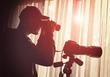Uomo con il binocolo e controllo della telecamera qualcuno Archivio Fotografico - 37230487