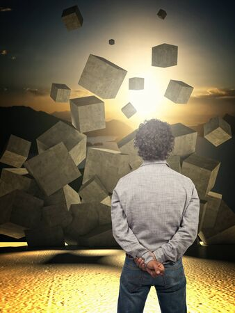 falling cubes: man look croncrete abstract cubes falling from the sky Stock Photo