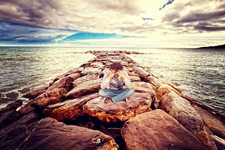 desesperado: desesperado hombre sentado en la roca del mar Foto de archivo