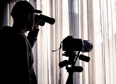man with binoculars and camera control someone Foto de archivo