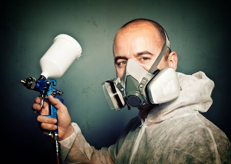 worker with spray-gun and protection clothes