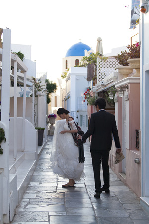 formal dress: Oia,Santorini, GREECE - June 14, 2015:married couple in formal dress looking for a nice place for picture