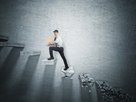 broken wall: smiling delivery man and fallen broken step Stock Photo