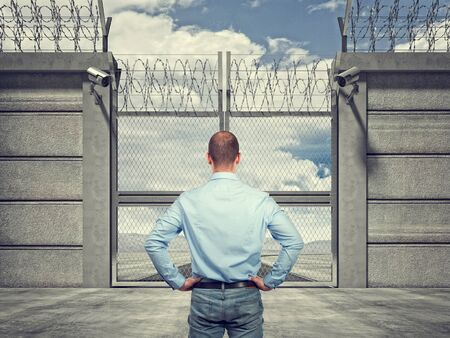 keepout: 3d image of security border line gate with razor wire and man Stock Photo