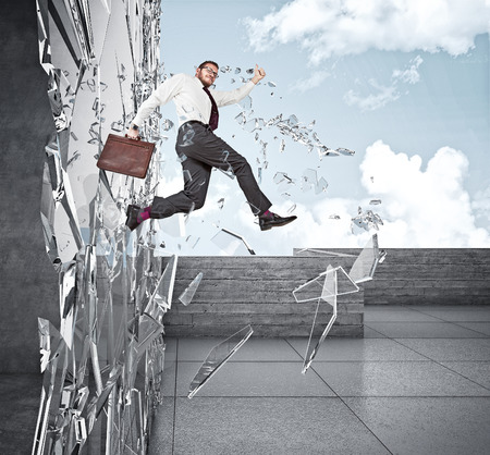 broke: smiling businessman broke glass with jump Stock Photo
