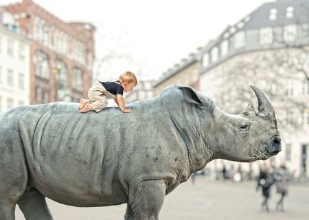little child on huge rhino