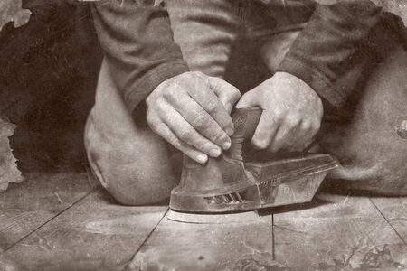 craftman: closeup of carpenter work with sander on wood floor