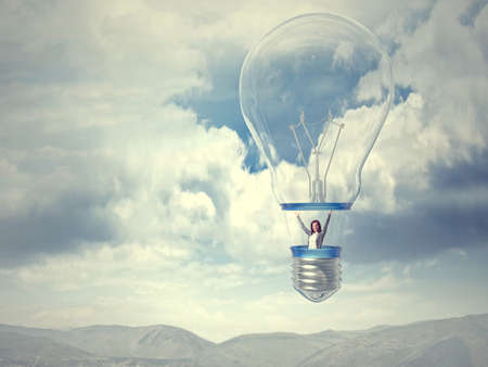 invent clever: smiling woman on bulb balloon Stock Photo