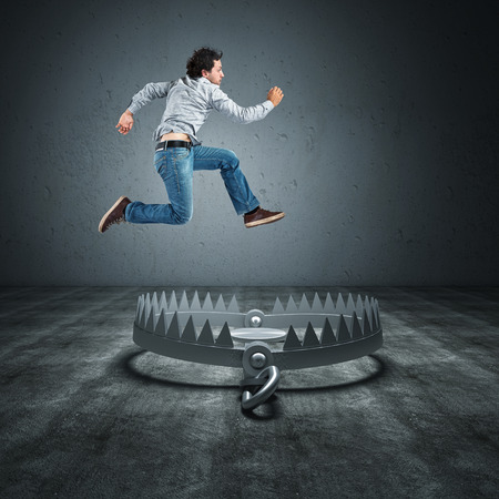 casual business man: worker jump over bear trap