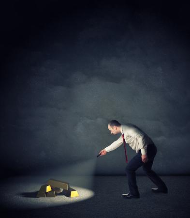 ingot: businessman with flashlight find gold ingot