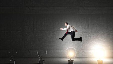 brillant: man jump over 3d bulb concept of idea Stock Photo