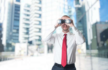 man with binoculars building background Stock Photo