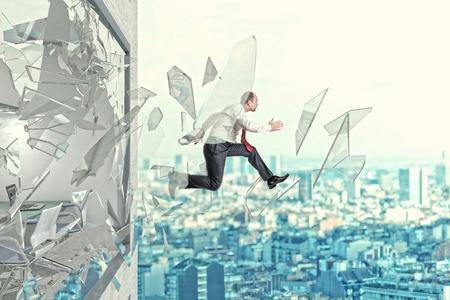 homme d'affaires saut dehors de sa fenêtre de rupture de bureau