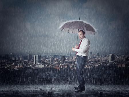 man with umbrella and heavy rain urban background
