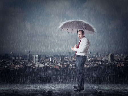 uomo sotto la pioggia: Uomo con l'ombrello e la pioggia battente di fondo urbano Archivio Fotografico