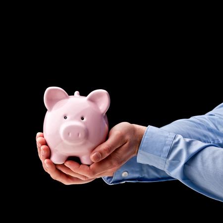 business funds: mans hands hold classic piggybank