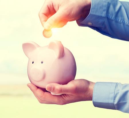 business funds: man put euro coin in piggybank Stock Photo