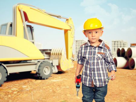helmet construction: little handyman at construction site Stock Photo