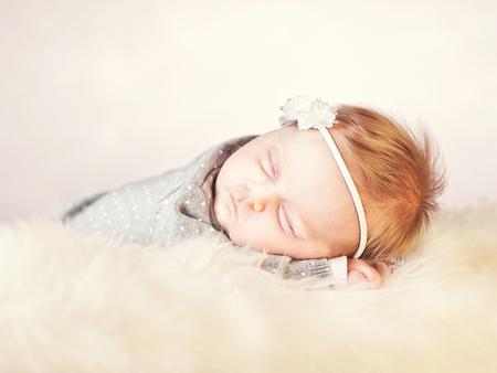 femal: sleeping femal baby on classic white fur Stock Photo