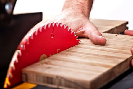 dangerous: detail of table saw blade and human hand in dangerous position