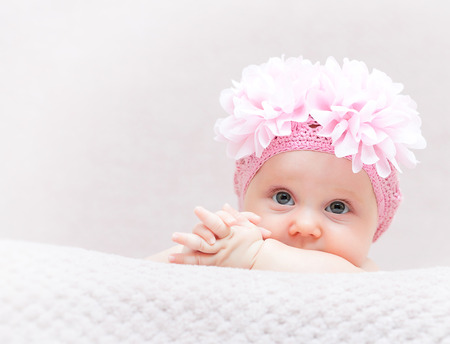 fineart: portrait of caucasian newborn with pink flower woolen hat