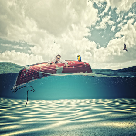businessman on inverted wood boat in the sea photo