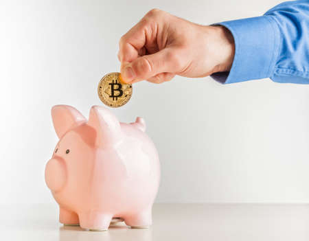 man put bitcoin coin in classic pink piggybank