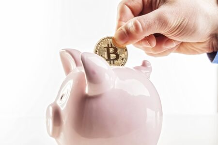 man put golden bitcoin in classic pink piggybank