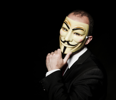 MILAN,ITALY, May 2017: Businessman wear anonymus mask in the dark .Editorial photo. Stock Photo