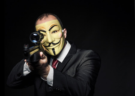 MILAN,ITALY, May 2017: Businessman wear anonymus mask and hold sniper rifle.Editorial photo.