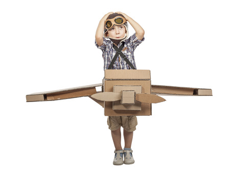 caucasian child play with cardboard airplane isolated on white background