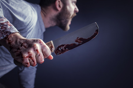 detail of man holding bloody knife crime concept